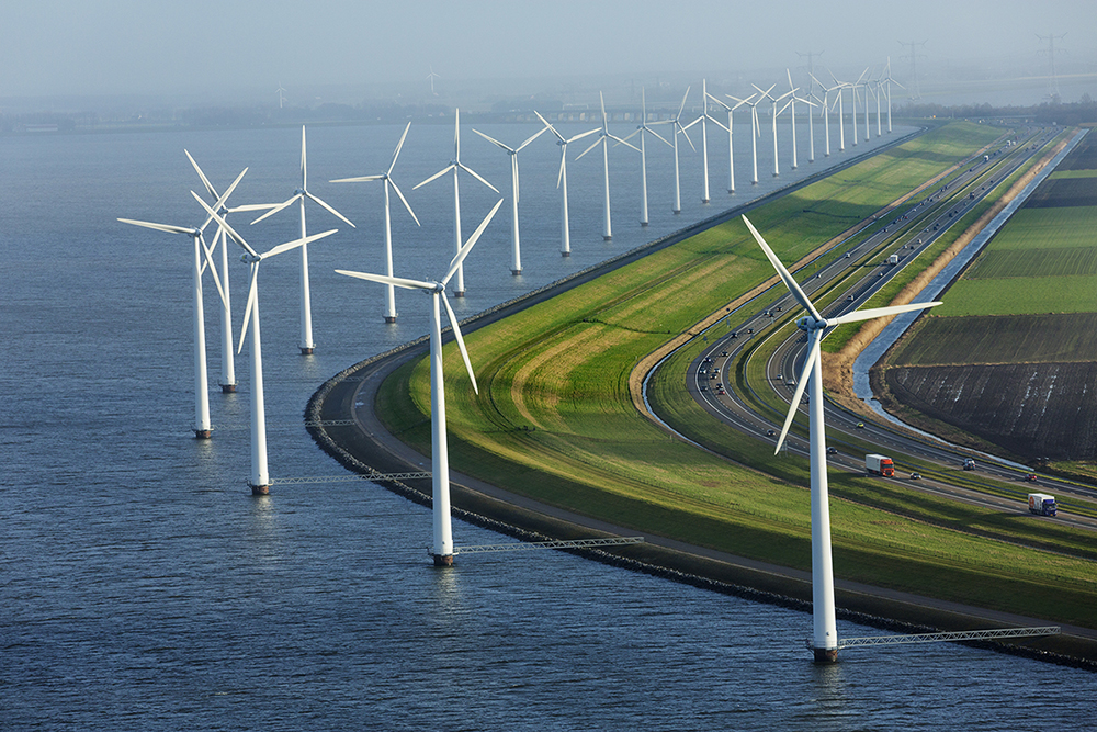 Windmills generate electricity along adjacent to the dyke that started turning tidal mudflats into farmland that is now the province of Flevoland.  Measuring 1419 sq km, it is almost wholly below sea level, and continues to drop as the land dries out, but is protected from the Zuiderzee by dkyes and electric pumps.